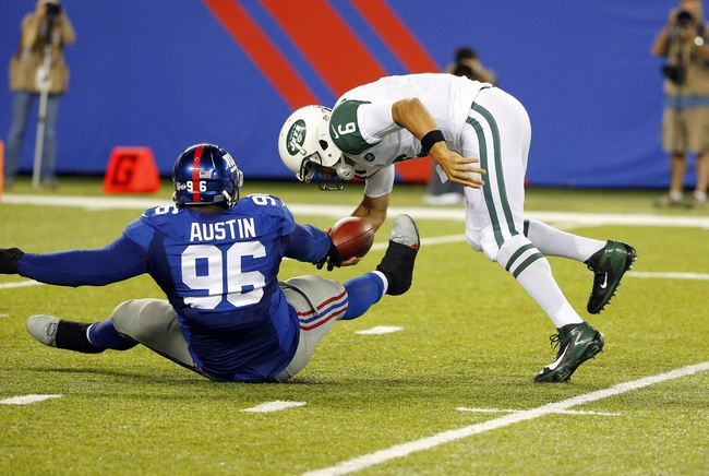 Aug 24, 2013; East Rutherford, NJ, USA; New York Giants defensive tackle Marvin Austin (96) throws New York Jets quarterback Mark Sanchez (6) to the ground for sack on his first ply from scrimmage during the second half at MetLife Stadium. New York Jets defeat the New York Giants 24-21 in OT. Mandatory Credit: Jim O'Connor-USA TODAY Sports