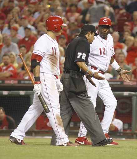 Aug 24, 2013; Cincinnati, OH, USA; Cincinnati Reds manager Dusty Baker (12) argues with home plate umpire Alfonso Marquez (72) after Reds center fielder Shin-Soo Choo (17) thought he was hit by a pitch in the sixth inning at Great American Ball Park. The Reds defeated the Brewers 6-3.Mandatory Credit: David Kohl-USA TODAY Sports