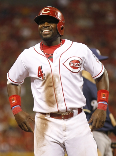 Aug 24, 2013; Cincinnati, OH, USA; Cincinnati Reds second baseman Brandon Phillips (4) smiles as he stands on base during a game against the Milwaukee Brewers at Great American Ball Park. The Reds defeated the Brewers 6-3.Mandatory Credit: David Kohl-USA TODAY Sports