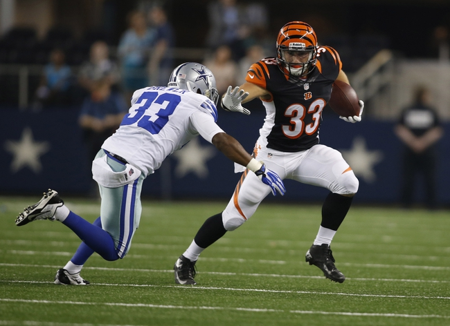 Aug 24, 2013; Arlington, TX, USA; Cincinnati Bengals running back Rex Burkhead (33) tries to avoid a tackle by Dallas Cowboys defensive back Xavier Brewer (33) during the fourth quarter at AT&T Stadium.  The Cowboys won 24-18. Mandatory Credit: Tim Heitman-USA TODAY Sports