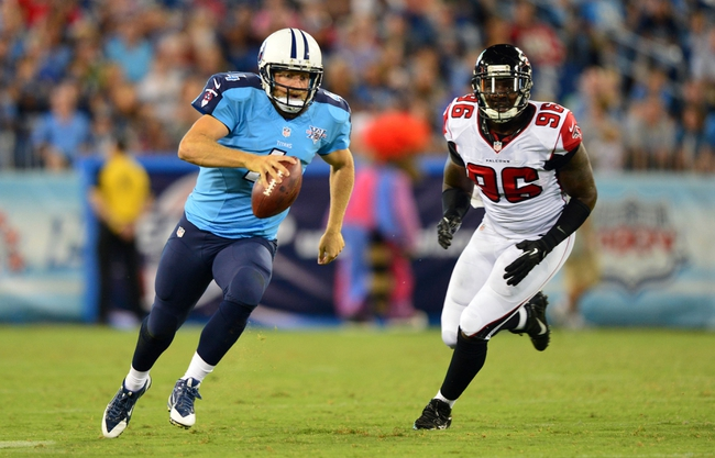 Aug 24, 2013; Nashville, TN, USA; Tennessee Titans quarterback Ryan Fitzpatrick (4) scrambles out of the pocket against Atlanta Falcons defensive end Jonathan Massaquoi (96) during the second half at LP Field. The Titans beat the Falcons 27-16. Mandatory Credit: Don McPeak-USA TODAY Sports