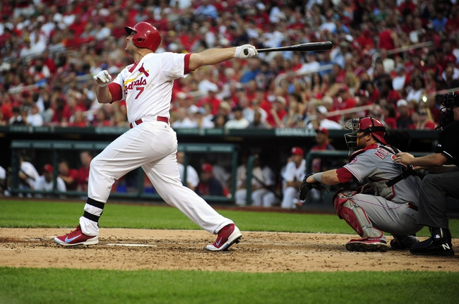 Aug 26, 2013; St. Louis, MO, USA; St. Louis Cardinals left fielder Matt Holliday (7) hits a three run home run off of Cincinnati Reds starting pitcher Mike Leake (not pictured) during the third inning at Busch Stadium. Mandatory Credit: Jeff Curry-USA TODAY Sports