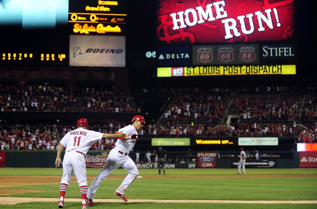 Aug 26, 2013; St. Louis, MO, USA; St. Louis Cardinals first baseman Allen Craig (21) is congratulated by third base coach Jose Oquendo (11) after hitting a grand slam off of Cincinnati Reds relief pitcher J.J. Hoover (not pictured) during the seventh inning at Busch Stadium. St. Louis defeated Cincinnati 8-6. Mandatory Credit: Jeff Curry-USA TODAY Sports