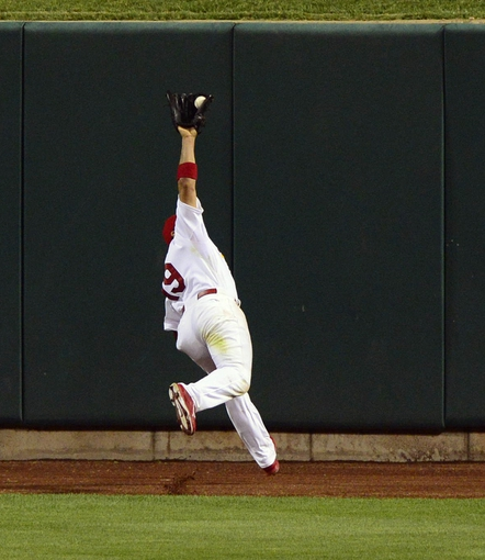 Aug 26, 2013; St. Louis, MO, USA; St. Louis Cardinals center fielder Jon Jay (19) catches a ball at the wall hit by Cincinnati Reds pinch hitter Chris Heisey (not pictured) during the ninth inning at Busch Stadium. St. Louis defeated Cincinnati 8-6. Mandatory Credit: Jeff Curry-USA TODAY Sports