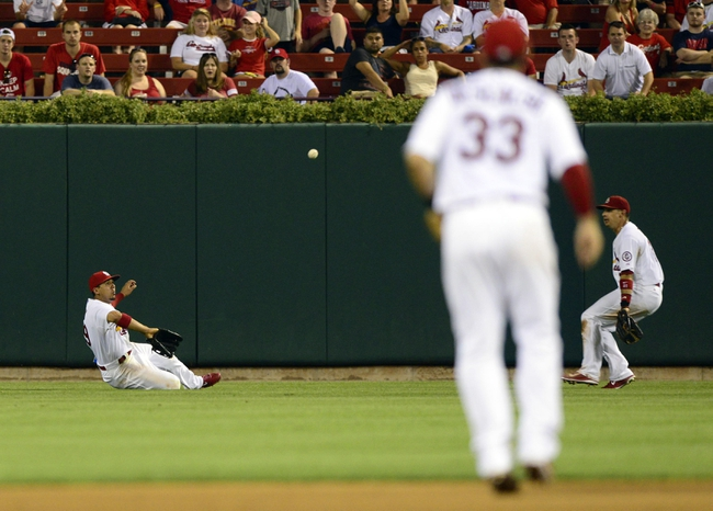 Aug 26, 2013; St. Louis, MO, USA; St. Louis Cardinals center fielder Jon Jay (19) slides and makes a catch on a ball hit by Cincinnati Reds first baseman Joey Votto (not pictured) during the seventh inning at Busch Stadium. St. Louis defeated Cincinnati 8-6. Mandatory Credit: Jeff Curry-USA TODAY Sports