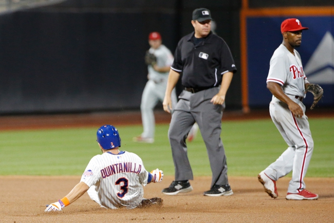 Aug 27, 2013; New York, NY, USA;  New York Mets shortstop Omar Quintanilla (3) slides to second on his double as Philadelphia Phillies shortstop Jimmy Rollins (11) waits for the ball during the fifth inning at Citi Field. Mandatory Credit: Anthony Gruppuso-USA TODAY Sports
