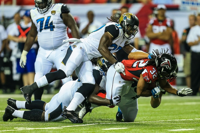 Aug 29, 2013; Atlanta, GA, USA; Atlanta Falcons running back Jacquizz Rodgers (32) is tackled by a gang of Jacksonville Jaguars in the first quarter at the Georgia Dome. Mandatory Credit: Daniel Shirey-USA TODAY Sports