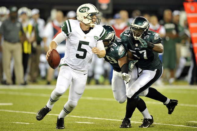 Aug 29, 2013; East Rutherford, NJ, USA; New York Jets quarterback Matt Simms (5) escapes the pressure of Philadelphia Eagles defensive end Everette Brown (57) and linebacker Adrian Robinson (49) during the second half of a preseason game at Metlife Stadium. The Jets won 27-20. Mandatory Credit: Joe Camporeale-USA TODAY Sports