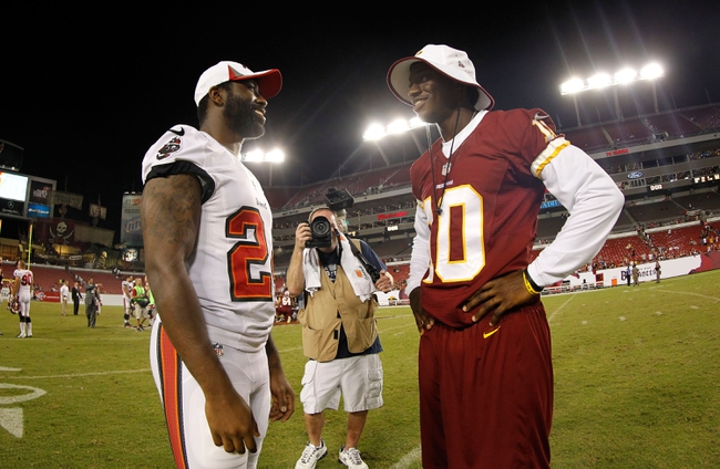 Aug 29, 2013; Tampa, FL, USA; Tampa Bay Buccaneers cornerback Darrelle Revis (24) and Washington Redskins quarterback Robert Griffin III (10) talk after the game at Raymond James Stadium. The Redskins won 30-12. Mandatory Credit: Kim Klement-USA TODAY Sports