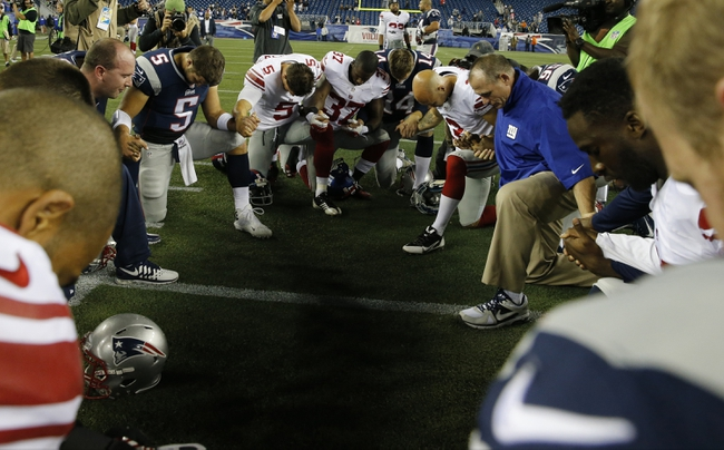 Aug 29, 2013; Foxborough, MA, USA; New England Patriots quarterback Tim Tebow (5) joins other players from his team and the New York Giants for a prayer on the field after the game Gillette Stadium. The Patriots defeated the Giants 28-20. Mandatory Credit: David Butler II-USA TODAY Sports