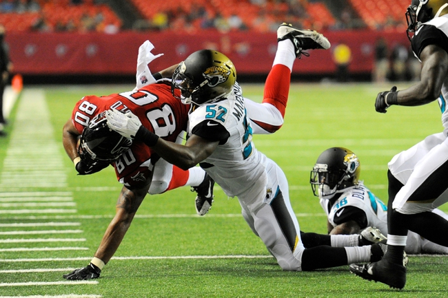 Aug 29, 2013; Atlanta, GA, USA; Atlanta Falcons tight end Levine Toilolo (80) is tackled by Jacksonville Jaguars linebacker Brandon Marshall (52) during the fourth quarter at the Georgia Dome. The Jaguars defeated the Falcons 20-16. Mandatory Credit: Dale Zanine-USA TODAY Sports