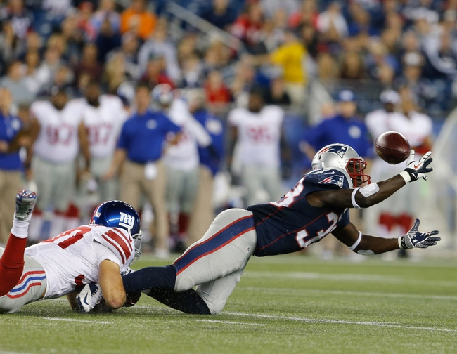 Aug 29, 2013; Foxborough, MA, USA; New England Patriots running back Leon Washington (33) fumbles the ball as New York Giants safety Cooper Taylor (30) defends on a punt return in the third quarter at Gillette Stadium. Mandatory Credit: David Butler II-USA TODAY Sports