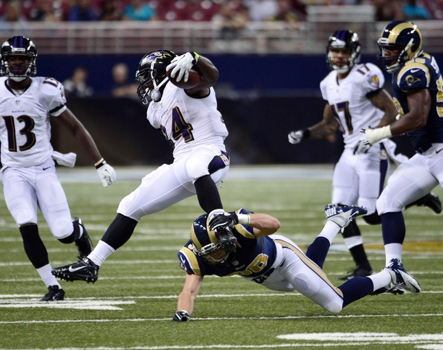 Aug 29, 2013; St. Louis, MO, USA; Baltimore Ravens running back Bobby Rainey (34) jumps away from St. Louis Rams defensive back Cody Davis (38) during the second half at the Edward Jones Dome. The Rams defeated the Ravens 24-21. Mandatory Credit: Scott Rovak-USA TODAY Sports