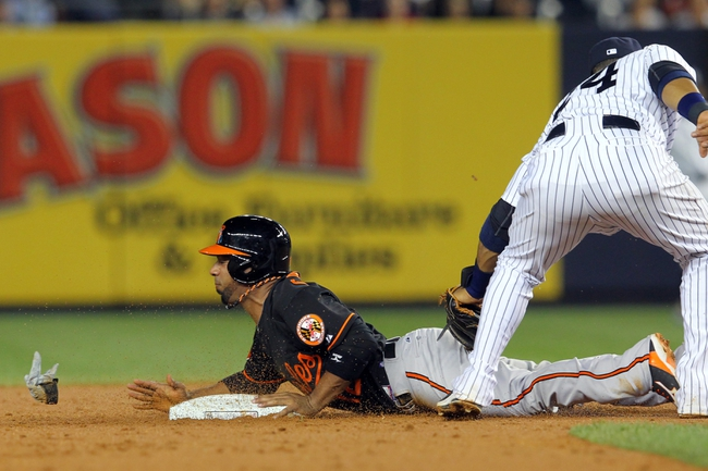 Aug 30, 2013; Bronx, NY, USA; Baltimore Orioles second baseman Alexi Casilla (12) steals second base ahead of a tag by New York Yankees second baseman Robinson Cano (24) during the fifth inning of a game at Yankee Stadium. Mandatory Credit: Brad Penner-USA TODAY Sports