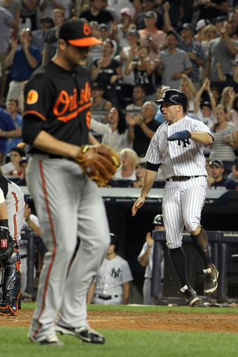 Aug 30, 2013; Bronx, NY, USA; New York Yankees center fielder Brett Gardner (11) reacts after scoring in front of Baltimore Orioles relief pitcher T.J. McFarland (66) during the fifth inning of a game at Yankee Stadium. Mandatory Credit: Brad Penner-USA TODAY Sports