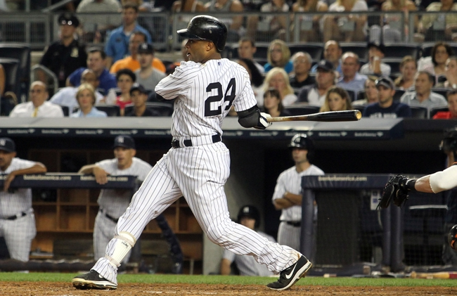 Aug 30, 2013; Bronx, NY, USA; New York Yankees second baseman Robinson Cano (24) hits a two RBI single against the Baltimore Orioles during the fifth inning of a game at Yankee Stadium. Mandatory Credit: Brad Penner-USA TODAY Sports
