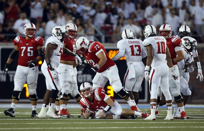 Aug 30, 2013; Dallas, TX, USA; Southern Methodist Mustangs quarterback Garrett Gilbert (11) lays on the ground after being sacked by the Texas Tech Red Raiders  defense at Gerald J. Ford Stadium. Mandatory Credit: Tim Heitman-USA TODAY Sports