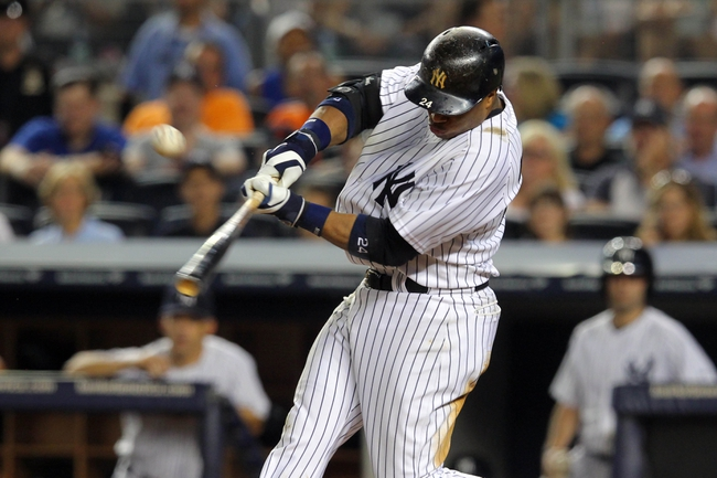 Aug 30, 2013; Bronx, NY, USA; New York Yankees second baseman Robinson Cano (24) hits a single against the Baltimore Orioles during the seventh inning of a game at Yankee Stadium. Mandatory Credit: Brad Penner-USA TODAY Sports
