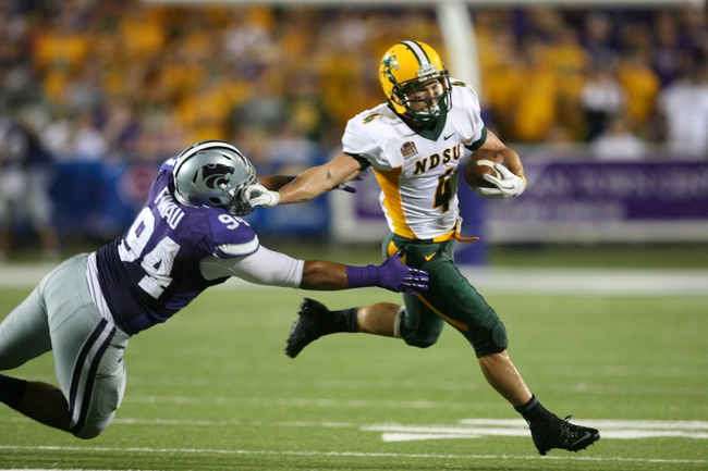 Aug 30, 2013; Manhattan, KS, USA; North Dakota State Bison wide receiver Ryan Smith (4) runs by Kansas State Wildcats defensive end Alauna Finau (94) during the Bisons' 24-21 win at Bill Snyder Family Stadium. Mandatory Credit: Scott Sewell-USA TODAY Sports