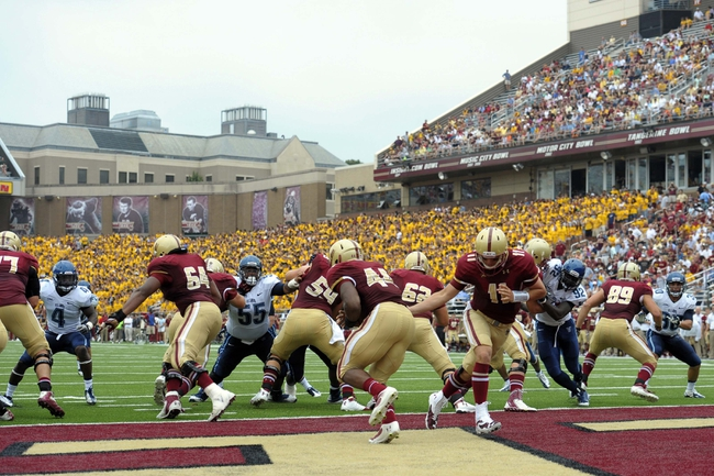 Aug 31, 2013; Boston, MA, USA; Boston College Eagles quarterback Chase Rettig (11) hands the ball off to running back Andre Williams (44) during the first half against the Villanova Wildcats at Alumni Stadium. Mandatory Credit: Bob DeChiara-USA TODAY Sports