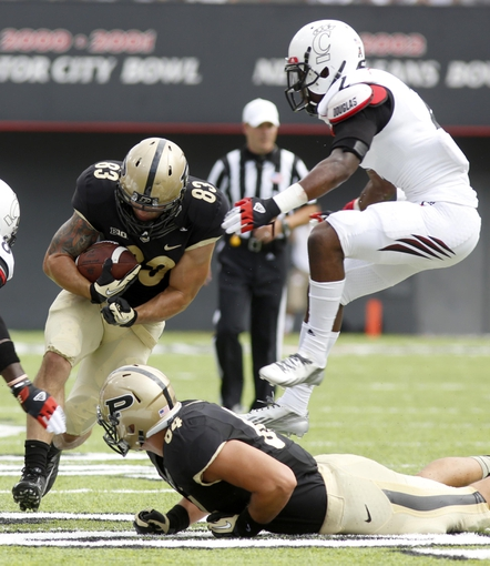 Aug 31, 2013; Cincinnati, OH, USA; Purdue Boilermakers wide receiver B.J. Knauf (83) runs through the middle against Cincinnati Bearcats cornerback Trenier Orr (right) during the second quarter at Nippert Stadium. Mandatory Credit: David Kohl-USA TODAY Sports