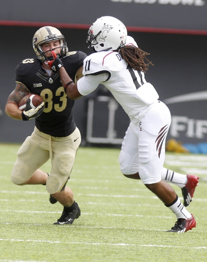 Aug 31, 2013; Cincinnati, OH, USA; Purdue Boilermakers wide receiver B.J. Knauf (83) runs for a gain against Cincinnati Bearcats cornerback Deven Drane (11) during the first quarter at Nippert Stadium. Mandatory Credit: David Kohl-USA TODAY Sports