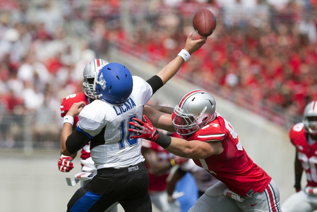 Aug 31, 2013; Columbus, OH, USA; Buffalo Bulls quarterback Joe Licata (16) gets a pass away as he is hit by Ohio State Buckeyes defensive lineman Joey Bosa (97) at Ohio Stadium. Mandatory Credit: Greg Bartram-USA TODAY Sports