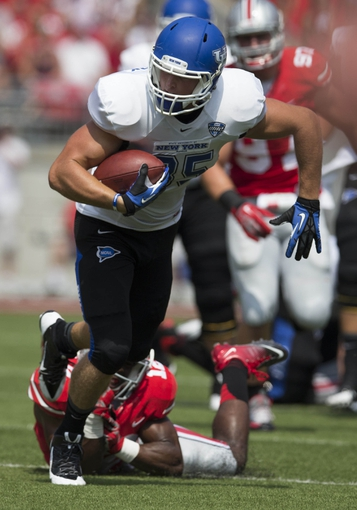 Aug 31, 2013; Columbus, OH, USA;Buffalo Bulls tight end Mason Schreck (85) breaks a tackle attempted by Ohio State Buckeyes cornerback Doran Grant (12) at Ohio Stadium. Mandatory Credit: Greg Bartram-USA TODAY Sports