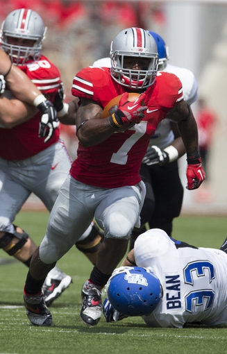 Aug 31, 2013; Columbus, OH, USA; Ohio State Buckeyes running back Jordan Hall (7) breaks a tackle attempted by Buffalo Bulls linebacker Blake Bean (33) on his way to his second touchdown of the game at Ohio Stadium. Mandatory Credit: Greg Bartram-USA TODAY Sports