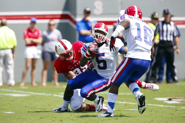 August 31, 2013; Raleigh, NC, USA;  Louisiana Tech D. J. Banks (5) is tacked by North Carolina State linebacker Brandon Pittman (39) after his 1st quarter catch at Carter Finley Stadium. Mandatory Credit: James Guillory-USA TODAY Sports