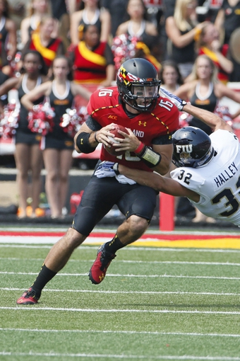 Aug 31, 2013; College Park, MD, USA; Maryland Terrapins quarterback C.J. Brown (16) runs for a gain against Florida International Panthers safety Justin Haley (32) at Byrd Stadium. Mandatory Credit: Mitch Stringer-USA TODAY Sports