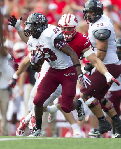 Aug 31, 2013; Madison, WI, USA; Massachusetts Minutemen running back Stacey Bedell (23) carries the football as Wisconsin Badgers defensive end Tyler Dippel (51) chases from behind during the third quarter at Camp Randall Stadium.  Wisconsin won 45-0.  Mandatory Credit: Jeff Hanisch-USA TODAY Sports