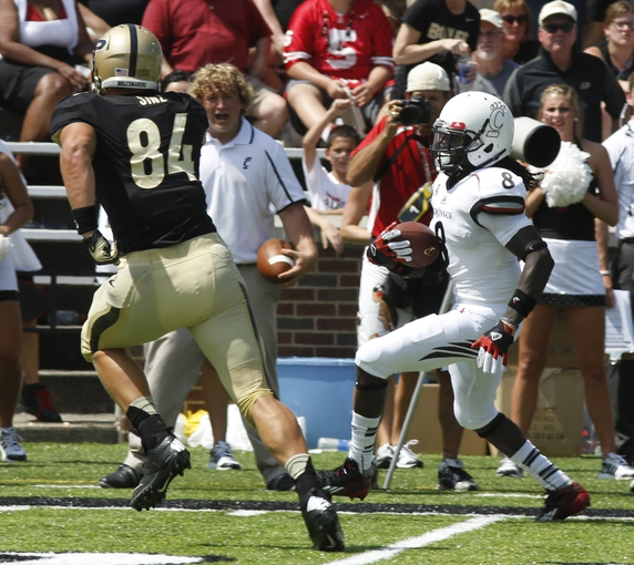 Aug 31, 2013; Cincinnati, OH, USA; Cincinnati Bearcats safety Adrian Witty (8) runs a 41 yard interception return past Purdue Boilermakers tight end Justin Sinz (84)  Nippert Stadium. Cincinnati won 42-7. Mandatory Credit: David Kohl-USA TODAY Sports