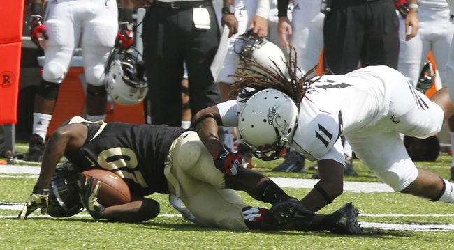 Aug 31, 2013; Cincinnati, OH, USA; Purdue Boilermakers running back Dalyn Dawkins (20) is brought down by Cincinnati Bearcats cornerback Deven Drane (11) during second half at Nippert Stadium. Cincinnati won 42-7. Mandatory Credit: David Kohl-USA TODAY Sports