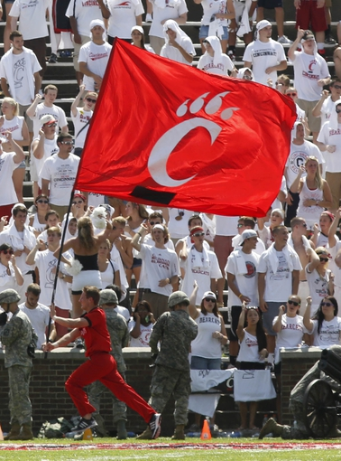 Aug 31, 2013; Cincinnati, OH, USA; Cincinnati Bearcats cheerleader runs past the crowd with a team flag during the fourth quarter at Nippert Stadium. Cincinnati beat the Purdue Boilermakers 42-7. Mandatory Credit: David Kohl-USA TODAY Sports