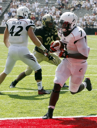 Aug 31, 2013; Cincinnati, OH, USA; Cincinnati Bearcats running back Tion Green (7) runs in a 1 yard touchdown against the Purdue Boilermakers during the fourth quarter at Nippert Stadium. Cincinnati won 42-7.Mandatory Credit: David Kohl-USA TODAY Sports