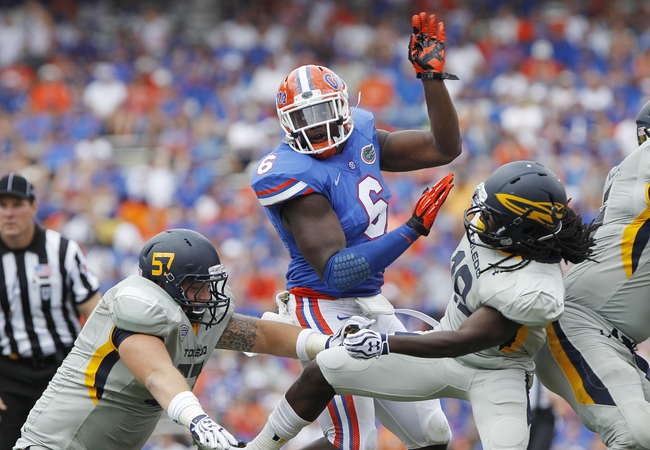 Aug 31, 2013; Gainesville, FL, USA; Florida Gators defensive end Dante Fowler Jr. (6) rushes past offensive linesman Robert Lisowski (57) and wide receiver Cassius McDowell (19) during the second half at Ben Hill Griffin Stadium. Florida Gators defeated the Toledo Rockets 24-6. Mandatory Credit: Kim Klement-USA TODAY Sports