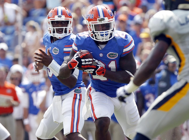 Aug 31, 2013; Gainesville, FL, USA; Florida Gators quarterback Tyler Murphy (3) hands the ball off to running back Kelvin Taylor (21) during the second half against the Toledo Rockets at Ben Hill Griffin Stadium. Florida Gators defeated the Toledo Rockets 24-6. Mandatory Credit: Kim Klement-USA TODAY Sports