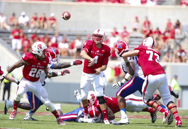 August 31, 2013; Raleigh, NC, USA;  North Carolina State quarterback Pet Thomas (4) throws a pass during the game against Louisiana Tech at Carter Finley Stadium. North Carolina State defeated Louisiana Tech 40-14. Mandatory Credit: James Guillory-USA TODAY Sports