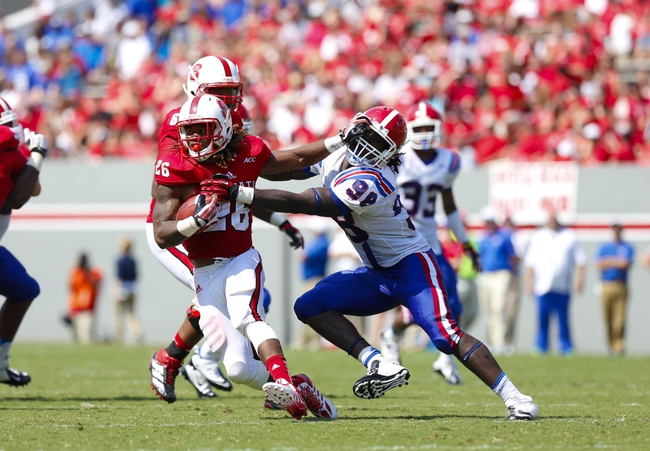August 31, 2013; Raleigh, NC, USA;  North Carolina State running back Tony Creecy (26) is tackled by the  Louisiana Tech defensive lineman Vontarrius Dora (98) at Carter Finley Stadium. North Carolina State defeated Louisiana Tech 40-14. Mandatory Credit: James Guillory-USA TODAY Sports