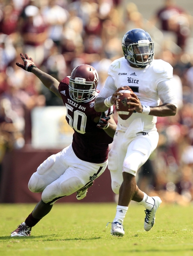 Aug 31, 2013; College Station, TX, USA; Rice Owls quarterback Driphus Jackson (5) scrambles from Texas A&M Aggies linebacker Tyrone Taylor (50) during the second half at Kyle Field. Texas A&M won 52-31. Mandatory Credit: Thomas Campbell-USA TODAY Sports