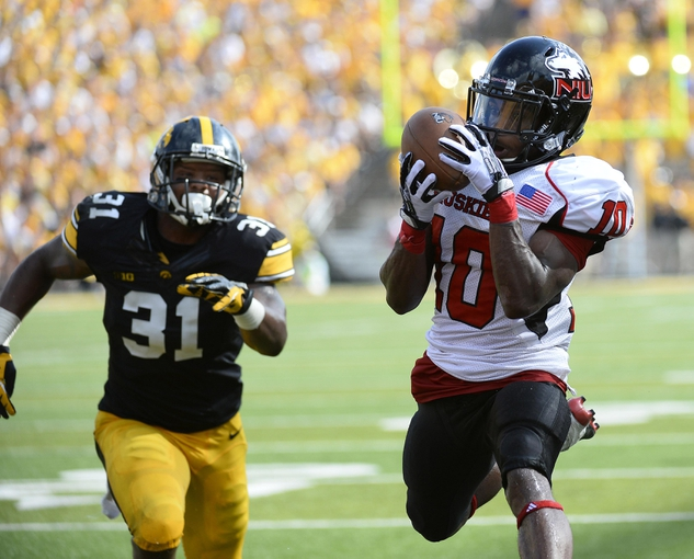 Aug 31, 2013; Iowa City, IA, USA; Northern Illinois Huskies wide receiver Tommylee Lewis (10) catches a touchdown against Iowa Hawkeyes defensive back John Lowdermilk (37) during the second quarter at Kinnick Stadium. Mandatory Credit: Mike DiNovo-USA TODAY Sports