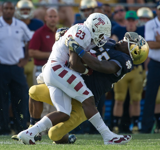 Aug 31, 2013; South Bend, IN, USA; Notre Dame Fighting Irish linebacker Prince Shembo (55) tackles Temple Owls halfback Zaire Williams (23) in the third quarter at Notre Dame Stadium. Notre Dame won 28-6. Mandatory Credit: Matt Cashore-USA TODAY Sports