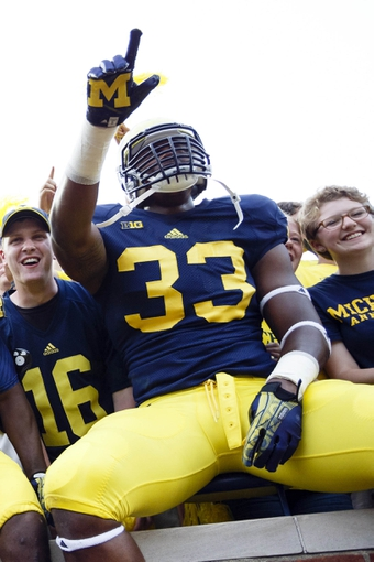 Aug 31, 2013; Ann Arbor, MI, USA; Michigan Wolverines defensive end Taco Charlton (33) celebrate with fans after the game against the Central Michigan Chippewas at Michigan Stadium. Michigan won 59-9. Mandatory Credit: Rick Osentoski-USA TODAY Sports