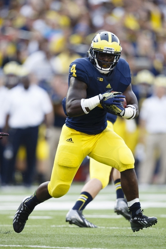 Aug 31, 2013; Ann Arbor, MI, USA; Michigan Wolverines running back De'Veon Smith (4) runs the ball second half against the Central Michigan Chippewas at Michigan Stadium. Mandatory Credit: Rick Osentoski-USA TODAY Sports