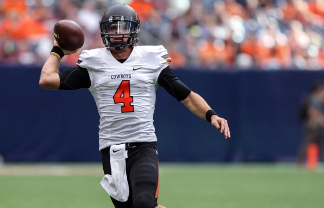 Aug 31, 2013; Houston, TX, USA; Oklahoma State Cowboys quarterback J.W. Walsh (4) looks for an open receiver during the third quarter against the Mississippi State Bulldogs at Reliant Stadium. Mandatory Credit: Troy Taormina-USA TODAY Sports