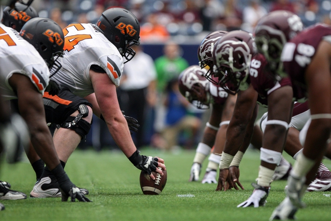 Aug 31, 2013; Houston, TX, USA; Oklahoma State Cowboys offensive linesman Jake Jenkins (54) snaps the ball during the third quarter against the Mississippi State Bulldogs at Reliant Stadium. Mandatory Credit: Troy Taormina-USA TODAY Sports