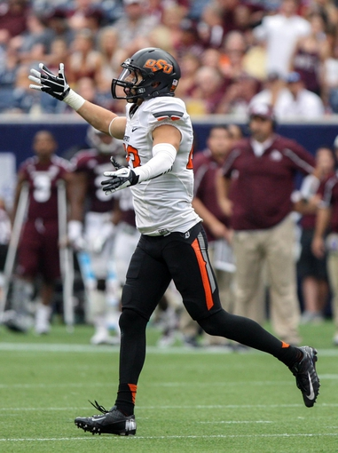 Aug 31, 2013; Houston, TX, USA; Oklahoma State Cowboys safety Zack Craig (23) celebrates after making an interception during the fourth quarter against the Mississippi State Bulldogs at Reliant Stadium. Mandatory Credit: Troy Taormina-USA TODAY Sports