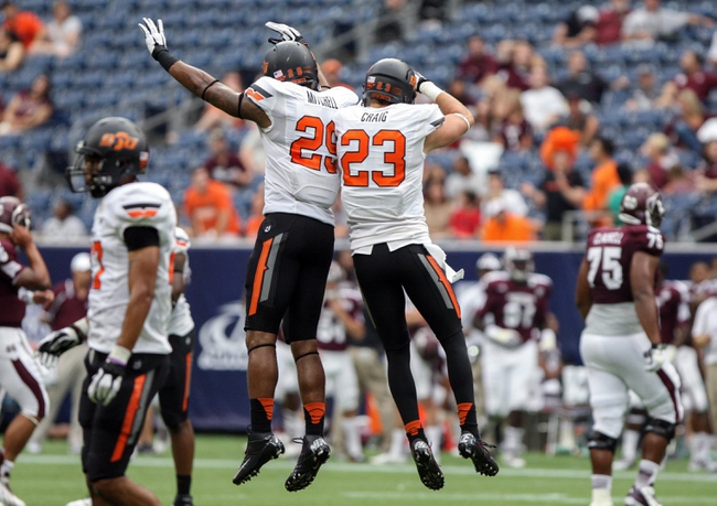 Aug 31, 2013; Houston, TX, USA; Oklahoma State Cowboys safety Zack Craig (23) and linebacker Joe Mitchell (29) celebrate after Craig makes an interception during the fourth quarter against the Mississippi State Bulldogs at Reliant Stadium. Mandatory Credit: Troy Taormina-USA TODAY Sports