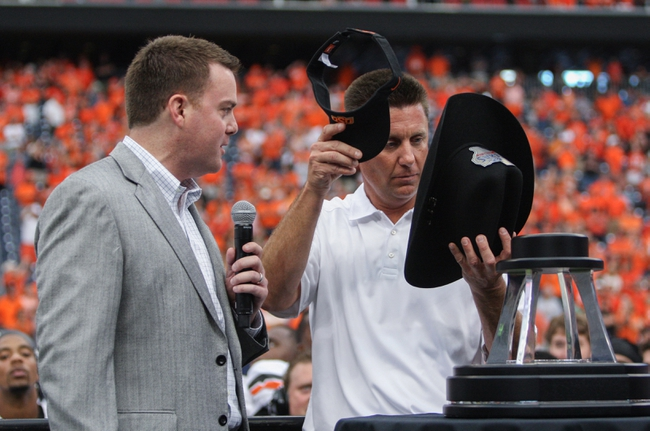 Aug 31, 2013; Houston, TX, USA; Oklahoma State Cowboys head coach Mike Gundy puts on a hat after defeating the Mississippi State Bulldogs 21-3 at Reliant Stadium. Mandatory Credit: Troy Taormina-USA TODAY Sports